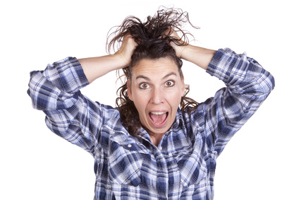 A woman is very frazzled with her hands in her hair.