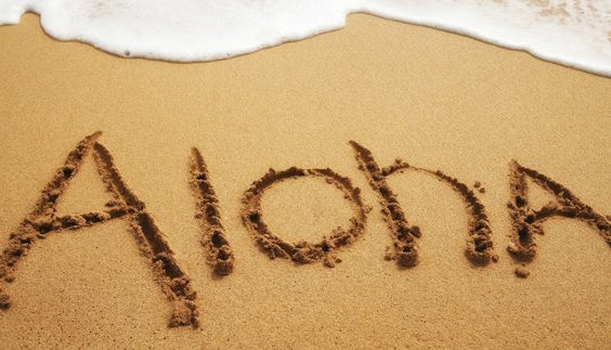 "Inviting ""Aloha"" written in soft beach sand with surf approaching."