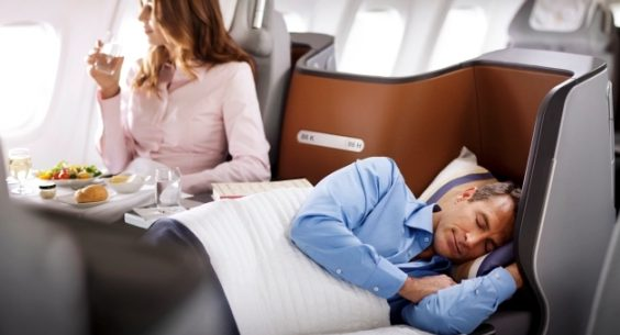 Ein Mann schläft im Bett der 747-8 Business Class. Eine Frau isst Salat  // A man is sleeping in a 747-8 Business Class bed. A woman is eating salad.