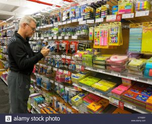 mature-man-checking-displays-in-staples-store-nyc-ETXE8Y