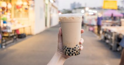 A young woman is holding a plastic cup of brown sugar bubble milk tea at a night market in Taiwan, Taiwan delicacy, close up.