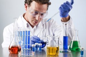 chemist working at a lab bench with various solutions